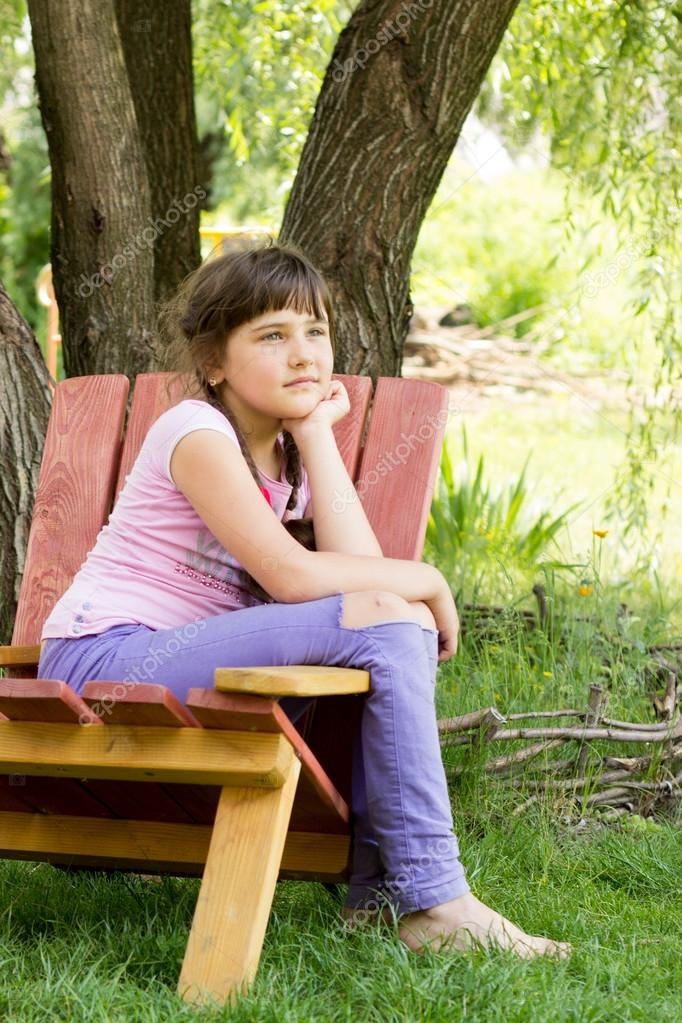 a little girl of 8 years, brunette in purple jeans, a pink T-shi