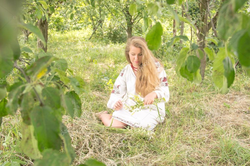 young girl, Ukrainian national costume, standing barefoot on the