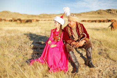 Kazakh man and woman in national costumes in the steppe playing dombyra and dancing