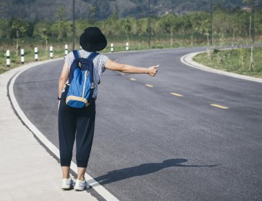 Teenager with Backpack Hitch Hiking on Highway road