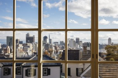 City view through window with blue sky and cloud