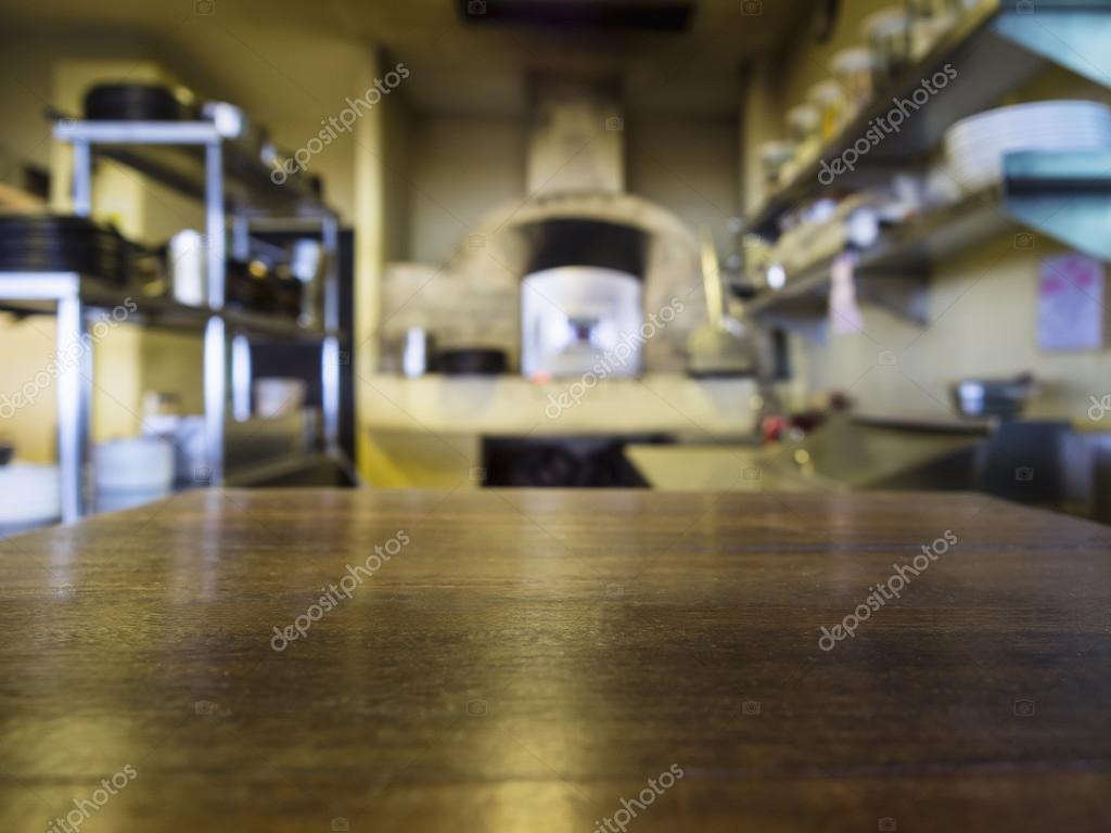 Restaurant Kitchen Background top of wooden table with blurred kitchen restaurant background