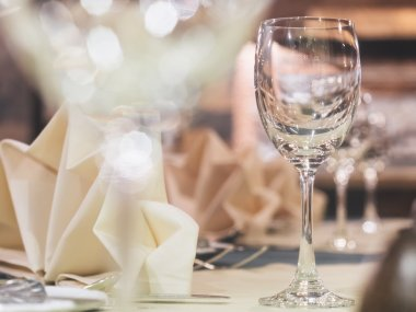 Empty glass on table with dining set with blurred restaurant