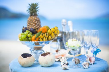 Wedding table with fruit and champagne on the background of the sea