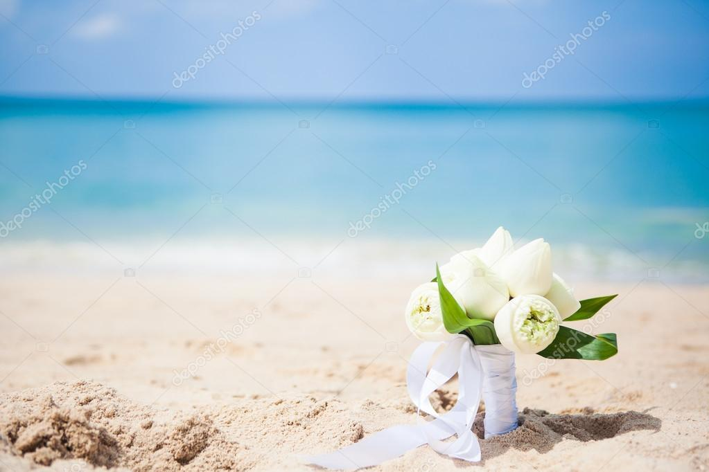 Wedding bouquet lotus on the background of the sea on the beach on old three grass