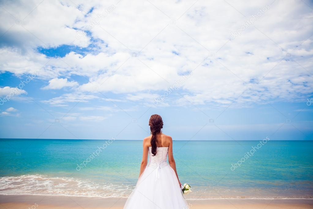 Bride Happy girl in a wedding dress by the sea beach background ocean