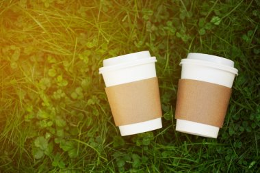 Two cups of coffee to go on the grass