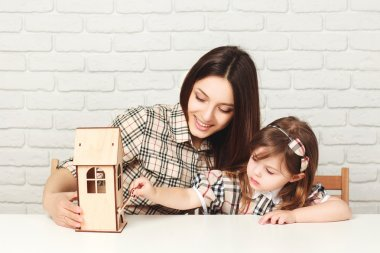 Young mother and daughter with little wooden house