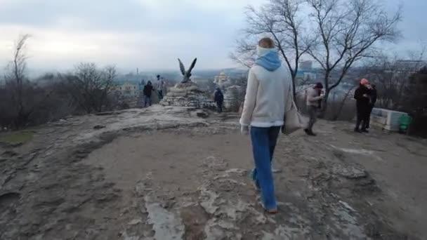 Pjatigorsk, Territorium Stawropol, Land Russland 01.01.2021 Ein Mädchen nähert sich einer Adlerskulptur auf einem Berg mit dem Namen Maschuk in der Nähe der Sehenswürdigkeiten, die Touristen fotografieren