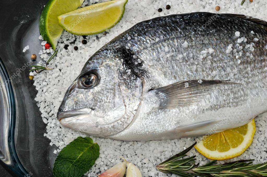 Pesci Di Dorado Sono In Piatto Di Vetro Con Sale Rosmarino Aglio