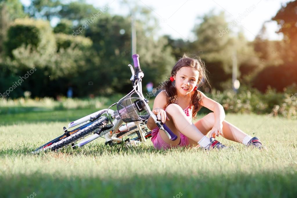 Niña Montando Su Bicicleta En Un Parque: Bicicleta Niño Niña A Caballo En El Atardecer De Verano