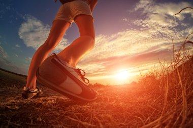 close up of feet sportwoman in autumn grass