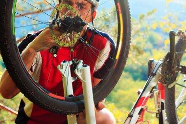 Man cyclist repairing a bike  against blue sky