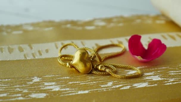 Přívěsek zlatý srdce tvar a červená růže na hadřík pozadí