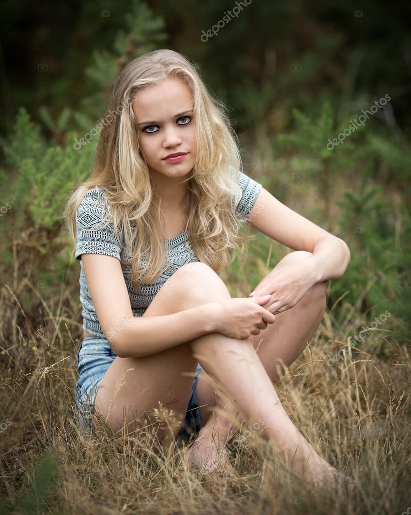 Mooie Blonde Tiener Zittend In Het Gras  Stockfoto  Heijo 103692060-4751