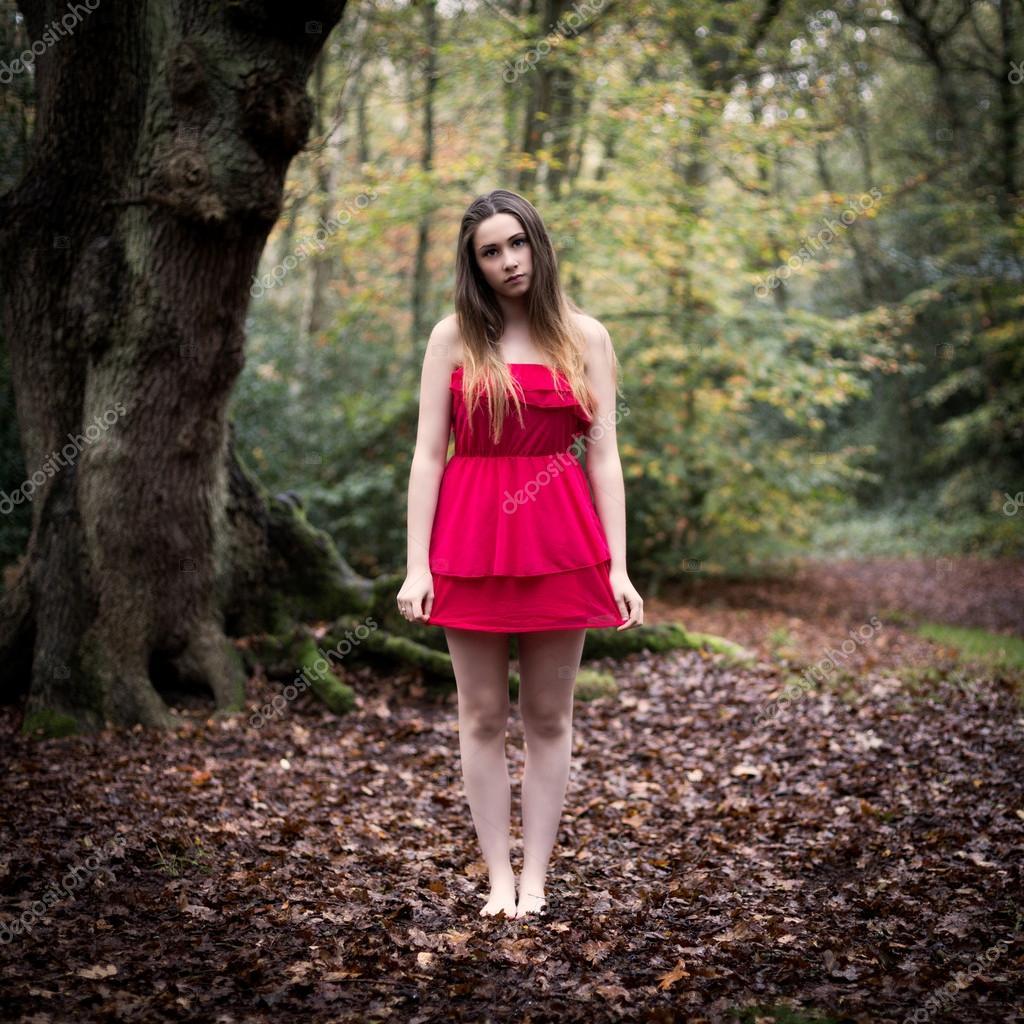Portret piękna nastolatka w krótkiej sukience stoi