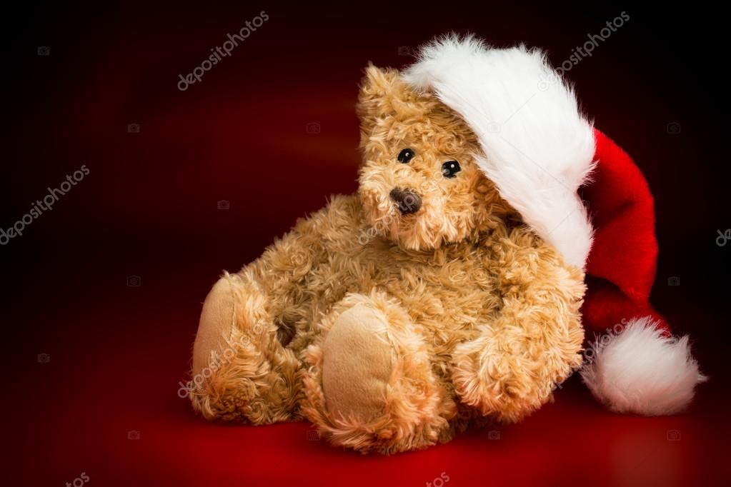 A brown teddy bear wearing a Christmas hat sitting isolated against a black  and red background — Foto de Heijo 629c281b173c