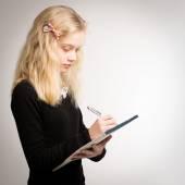 Teen blondýnka psaní poznámek na Poznámkový blok