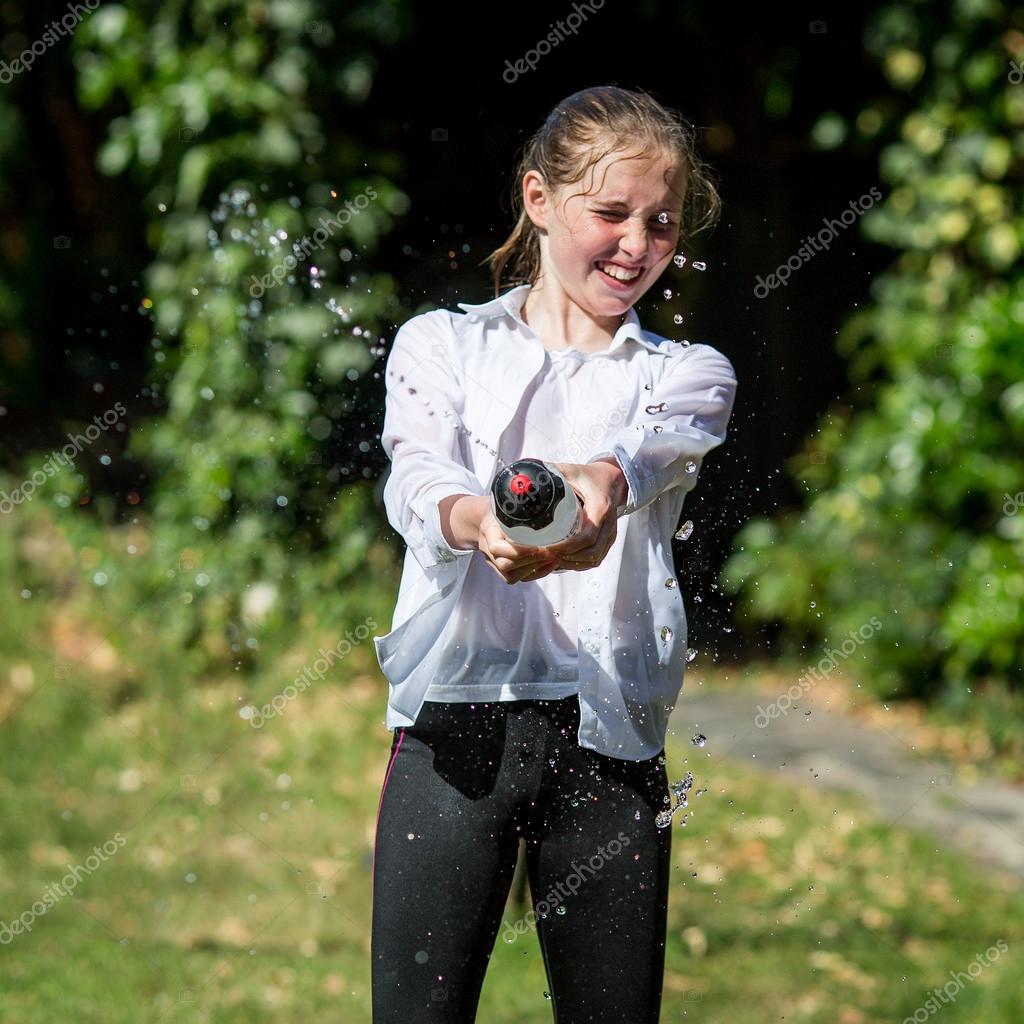 Wet Teenage Girl Squirts Water From Bottle  Stock Fotografie  Heijo 80542430-1098