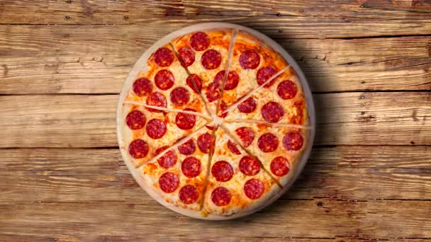 Video na pozadí feferonkové pizzy na dřevěném stole. Záběry.