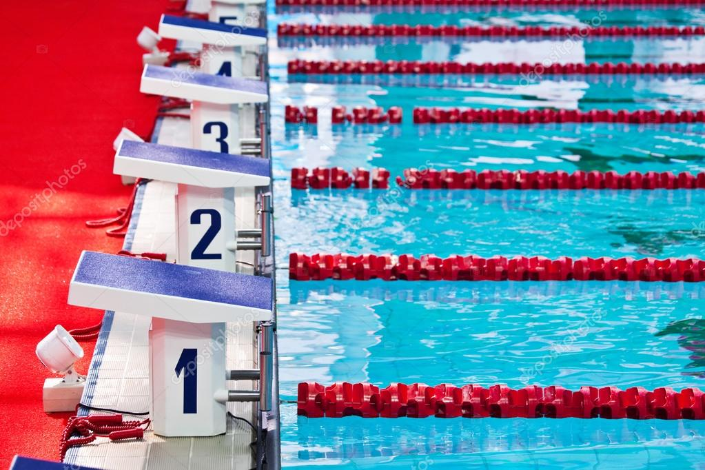 Swimming pool starting blocks — Stock Photo © ymgerman #77427070