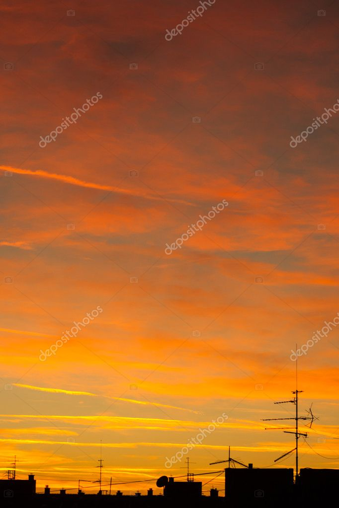 Urban sunset rooftops antenas and clouds