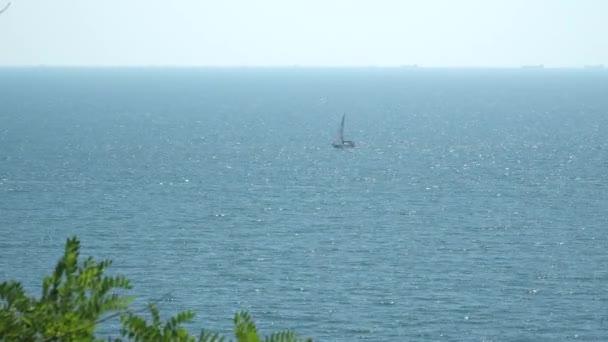 Pohled z pobřeží na loď, která plave v moři
