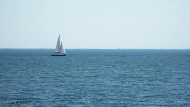 Jachta je pod plachtou plave v moři.