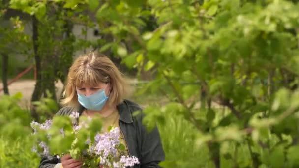 Eine junge Frau hält einen Strauß Flieder in ihren Händen. Die Frau trägt eine medizinische Maske auf dem Gesicht. Das Konzept Gesundheit und Sicherheit, COVID 19 Coronavirus Quarantäne, Virenschutz