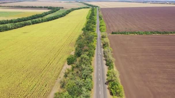 Dálnice mezi ornými poli a slunečnicovými poli. Zemědělská pole. Sklizeň. Letecký pohled.