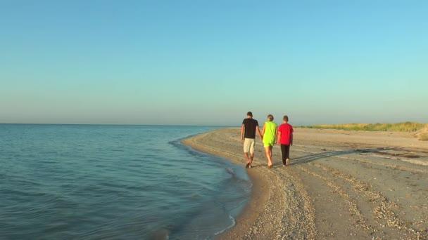 Mother and Child walking along the seashore at dawn