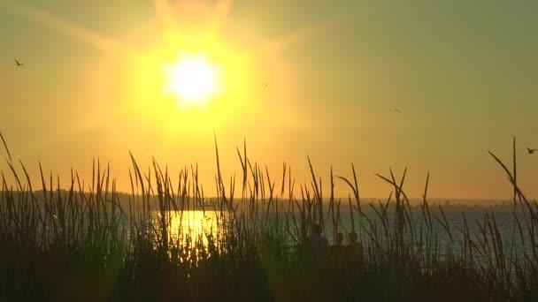 Rodina sledovat východ slunce nad mořem