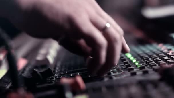 Zvukový inženýr, úprava fadery na stole mixážní konzole během živé akce.