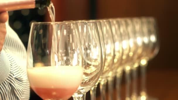 Sommelier ruka vylévající růžové víno do řádku s křišťálovými skly