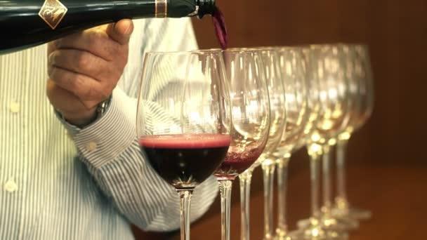 Sommelier ruka vylévající červené víno do řádku s křišťálovými skly