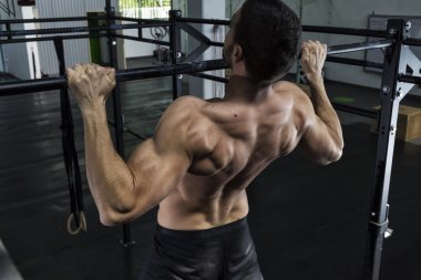 Bodybuilder doing pull ups at the gym