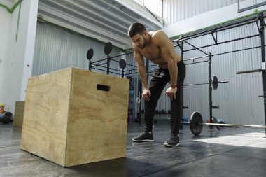 Bodybuilder working out at the gym ,box jumps