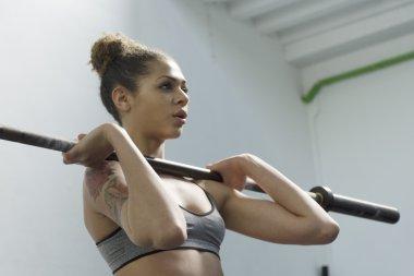 Girl lifting weight bar at the gym