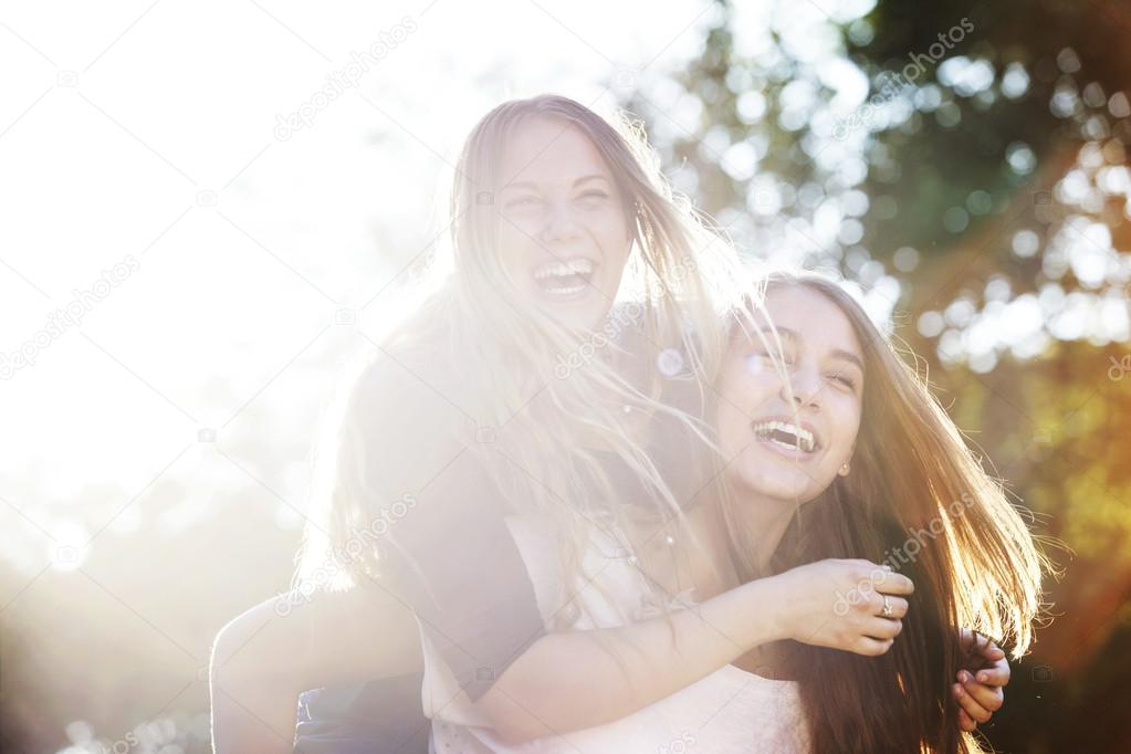 Two teenagers laughing at the park