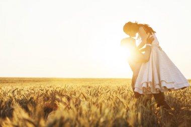 Groom lifting bride in the field of rye stock vector