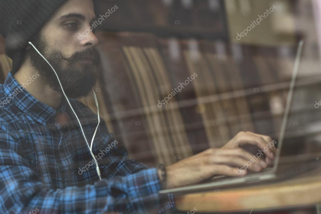 Young hipster man working on laptop in coffee shop
