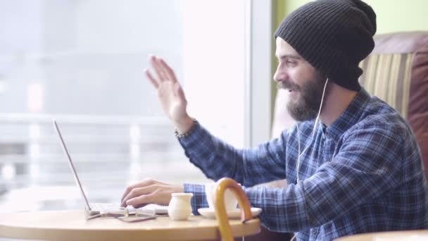 Mladá bederní módní člověk pracuje na notebooku v kavárně