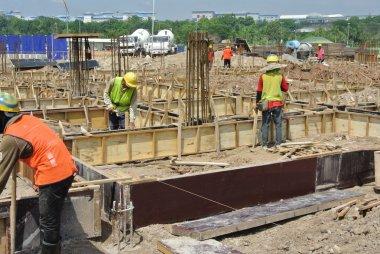 Construction workers fabricate ground beam formwork