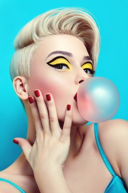 Fashionable girl with a stylish haircut inflates a chewing gum.