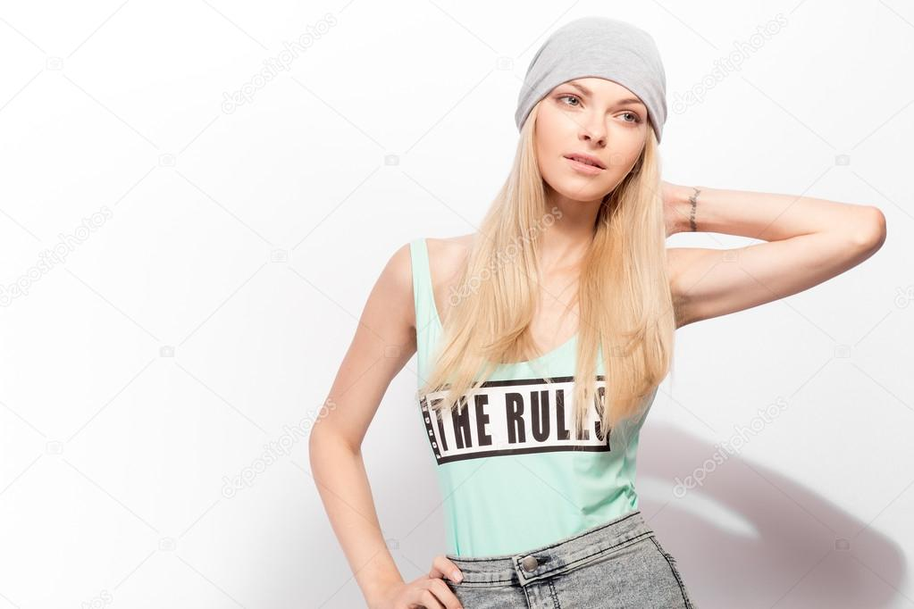 Young blonde model posing on a white background. Fasion shootina at the studio.