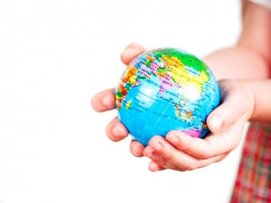 Hands of a child holding a globe