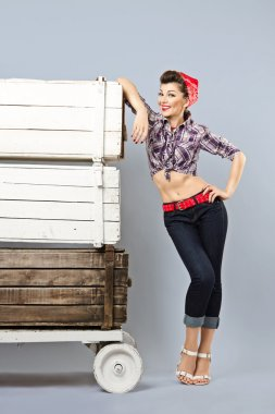 Funny pin-up girl storekeeper, stands with trolley