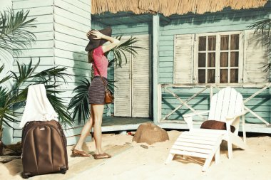 The young slender girl, happy examines bungalows on the island,