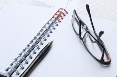 pen, notebook, glasses and financial report