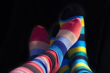 Colored socks on teenagers feet isolated on black
